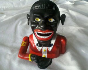 This early Americana Negro coin bank demonstrates features racist, exaggerated features of African Americans.