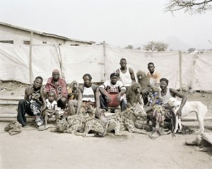 Men in Nigeria containing exotic animals such as: hyenas, pythons, and baboons.  Pieter Hugo. 2005-2007.