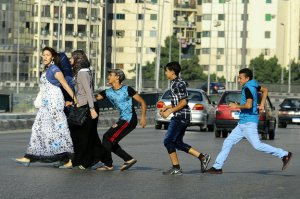 A young Egyptian man grabs a woman crossing the street with her friends in Cairo.